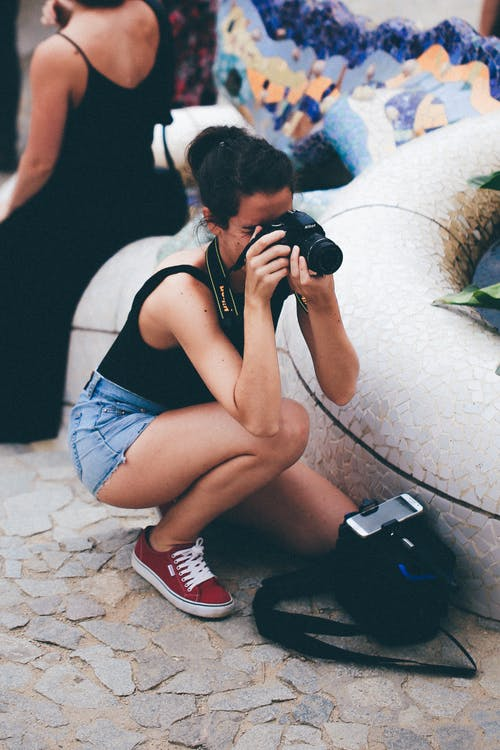 Woman in Black Tank Top Holding Dslr Camera