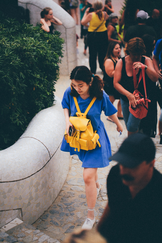 Woman in Blue Dress With Yellow Knapsack Walking Near People
