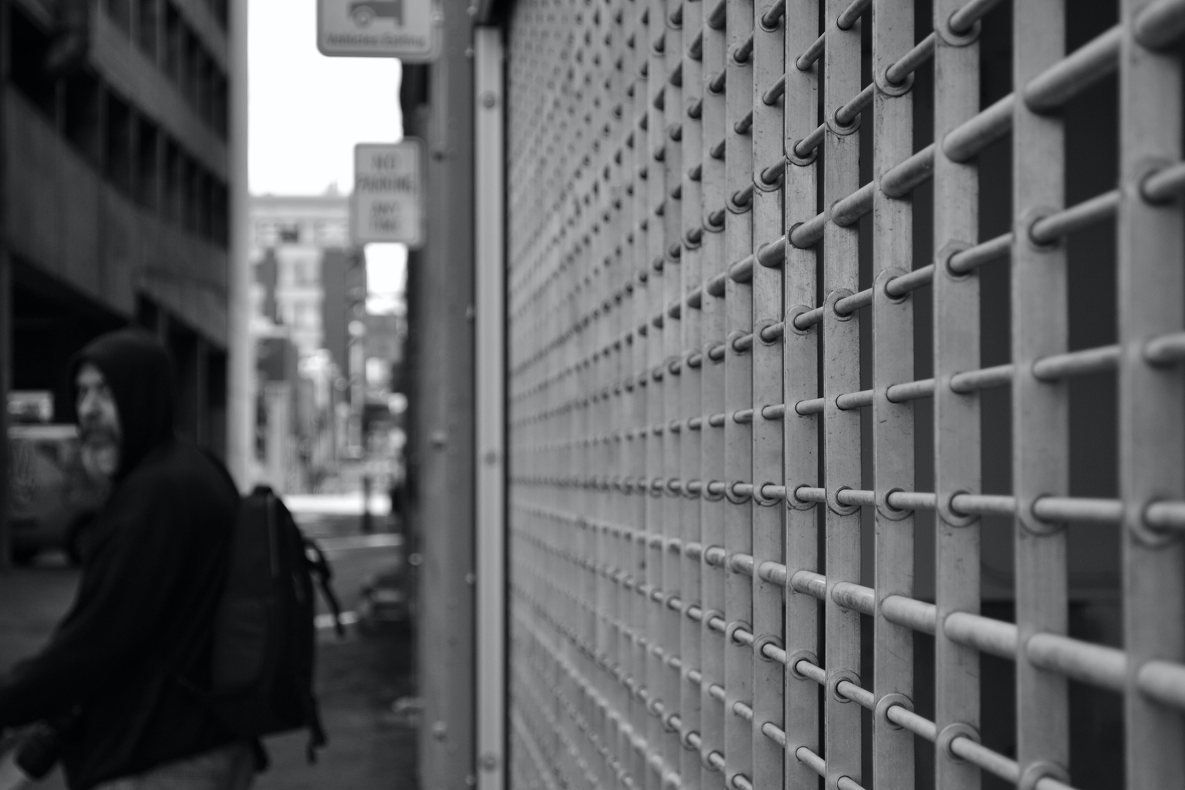 Grayscale Photo of Man in Hoodie in Front of White Window Grill
