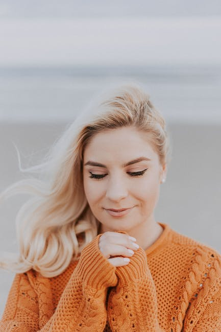Blonde Haired Woman in Orange Knitted Long-sleeved Top
