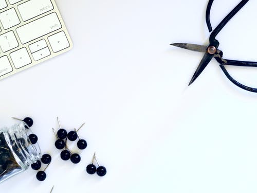 Flat Lay Photography of Black Pins Beside White Keyboard