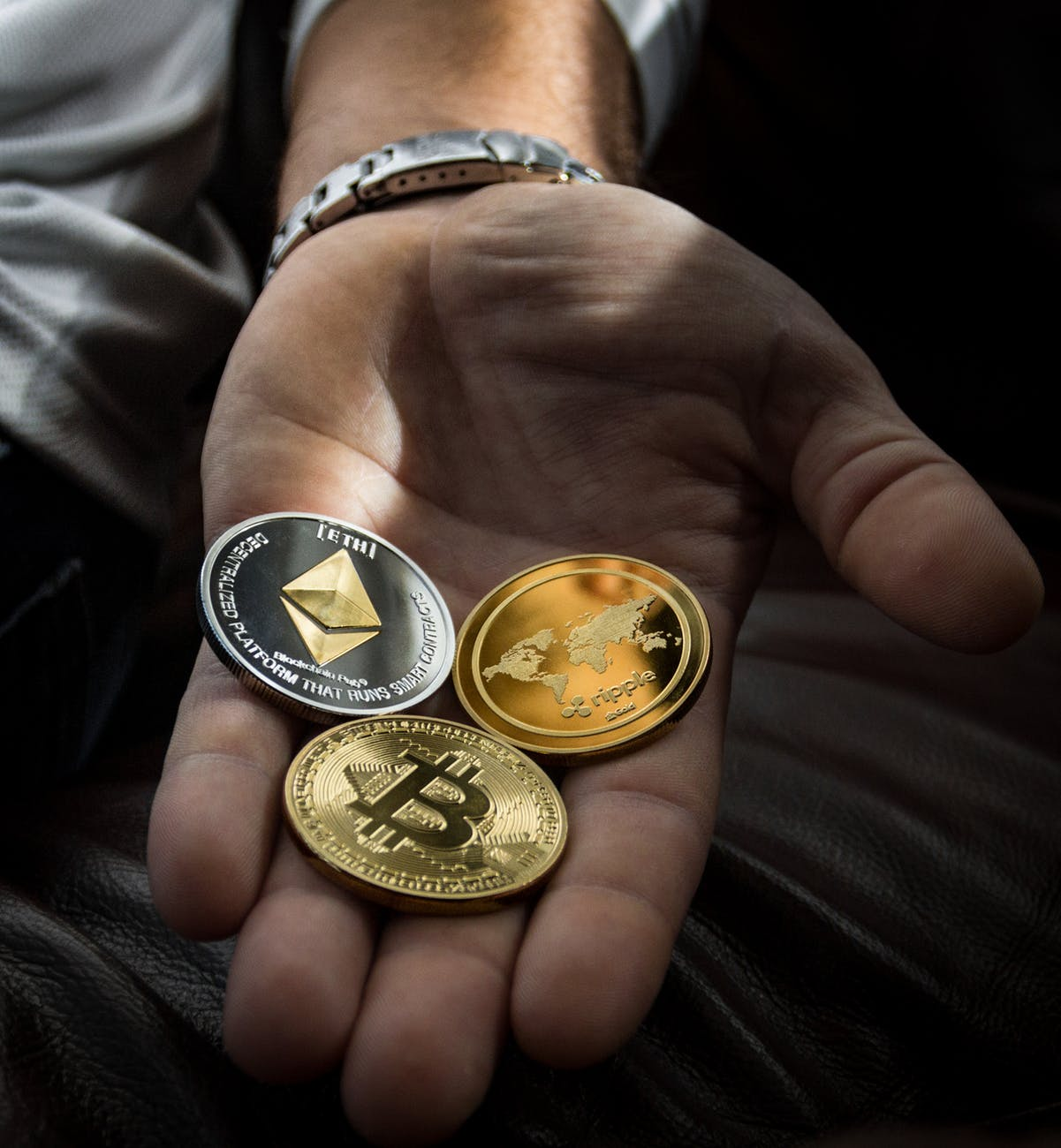 Man holding three cryptocurrencies