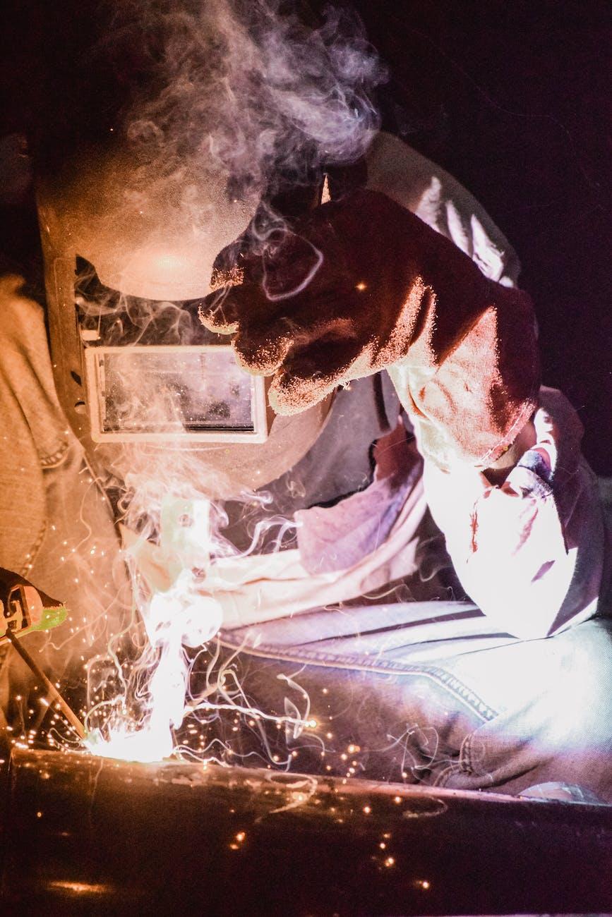 Man holding a welding helmet while welding a metal