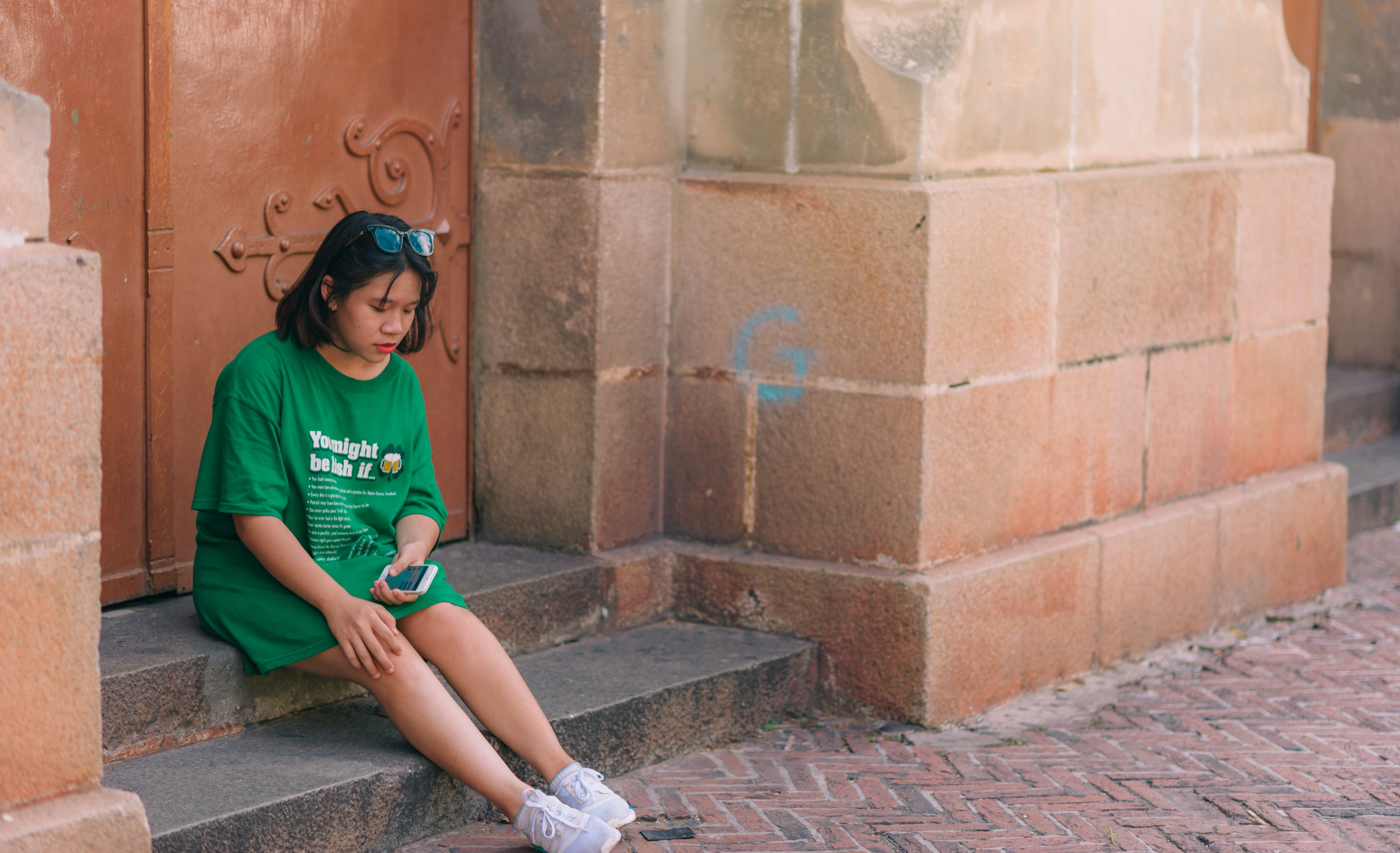 Woman Wearing Green Shirt Sitting Near Brown Gate Holding Smartphone