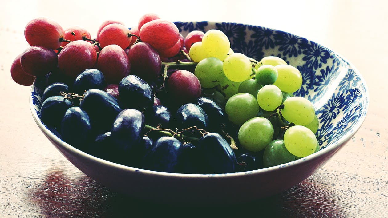 Red, Black, and Green Grapes in Round Blue and White Floral Ceramic Bowl