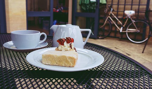 Cake on Ceramic Plate Near Teapot and Cups