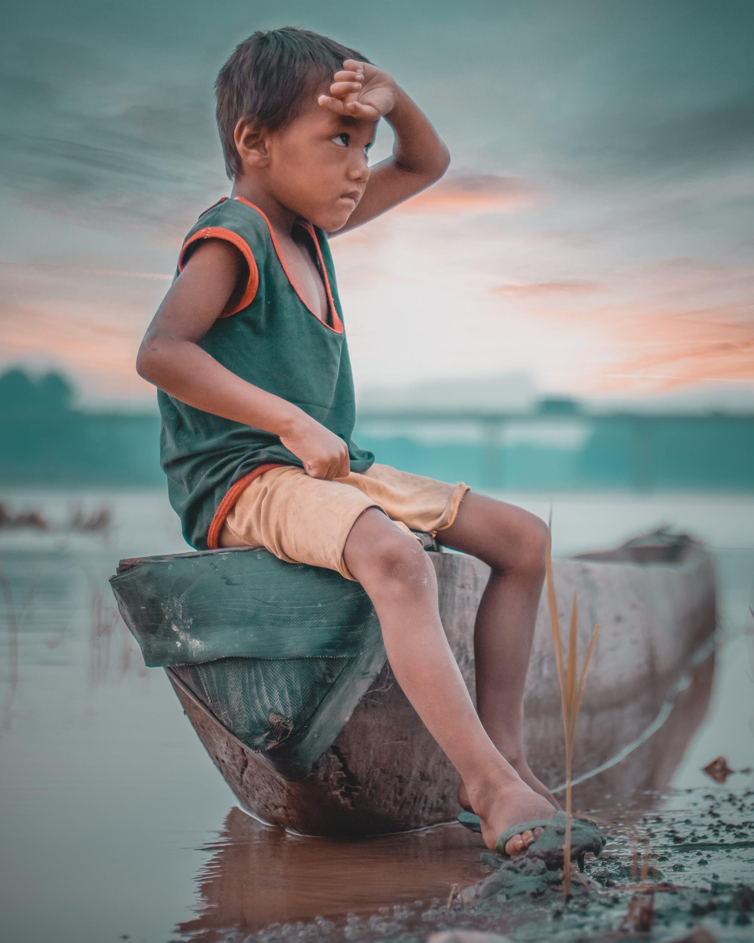 Boy Sitting on Canoe Near Body of Water Taken Under White Clouds