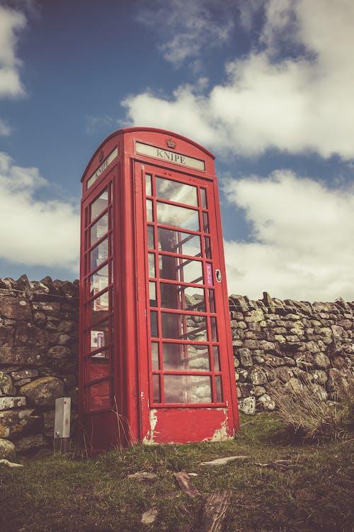 Foto d'estoc gratuïta de cabina telefònica, dia, herba, núvols