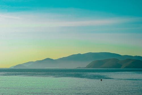 Body of Water Overlooking Islands Under Blue Daytime Sky