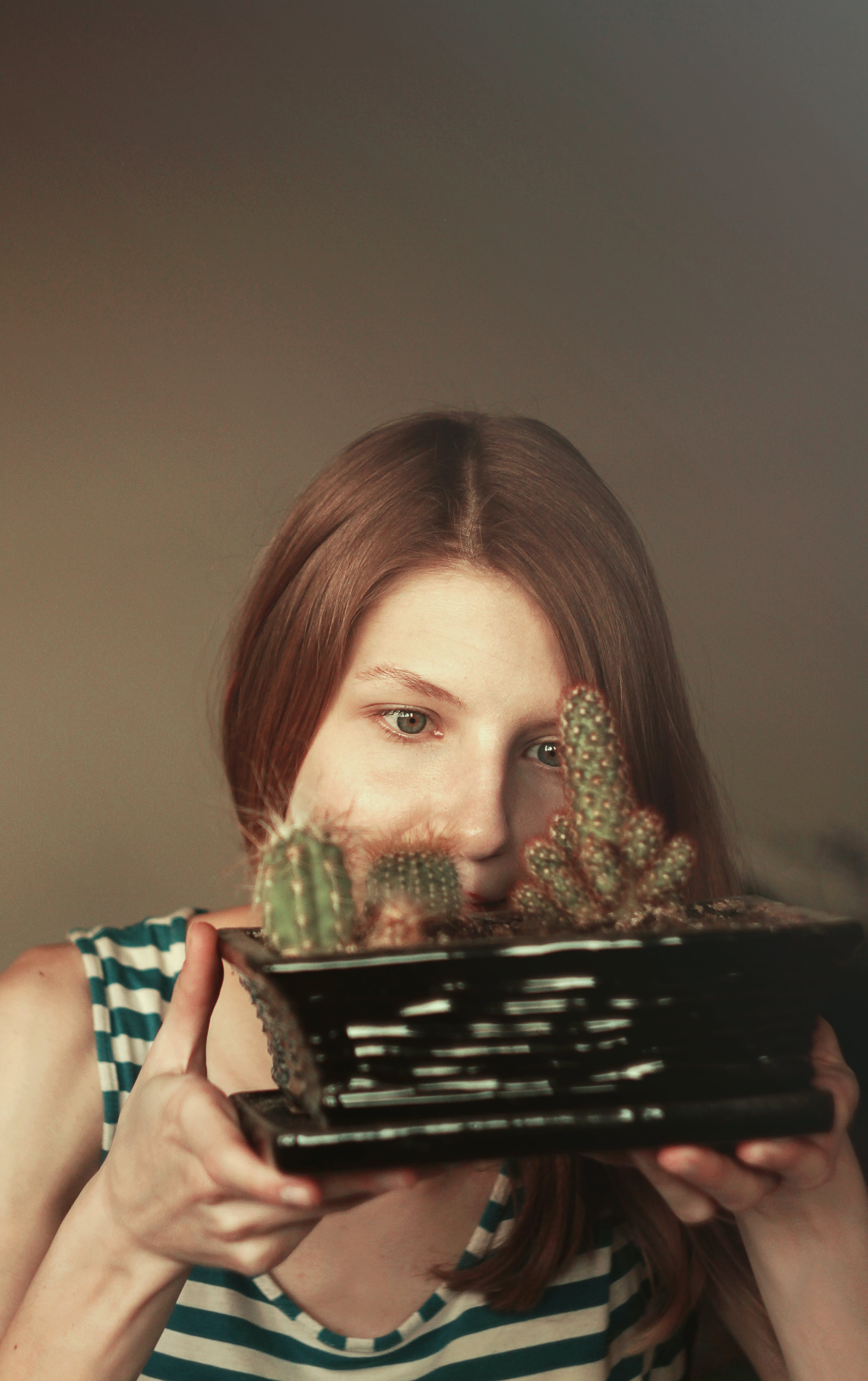 Woman Looking Closely to Cactus on Plant Pot