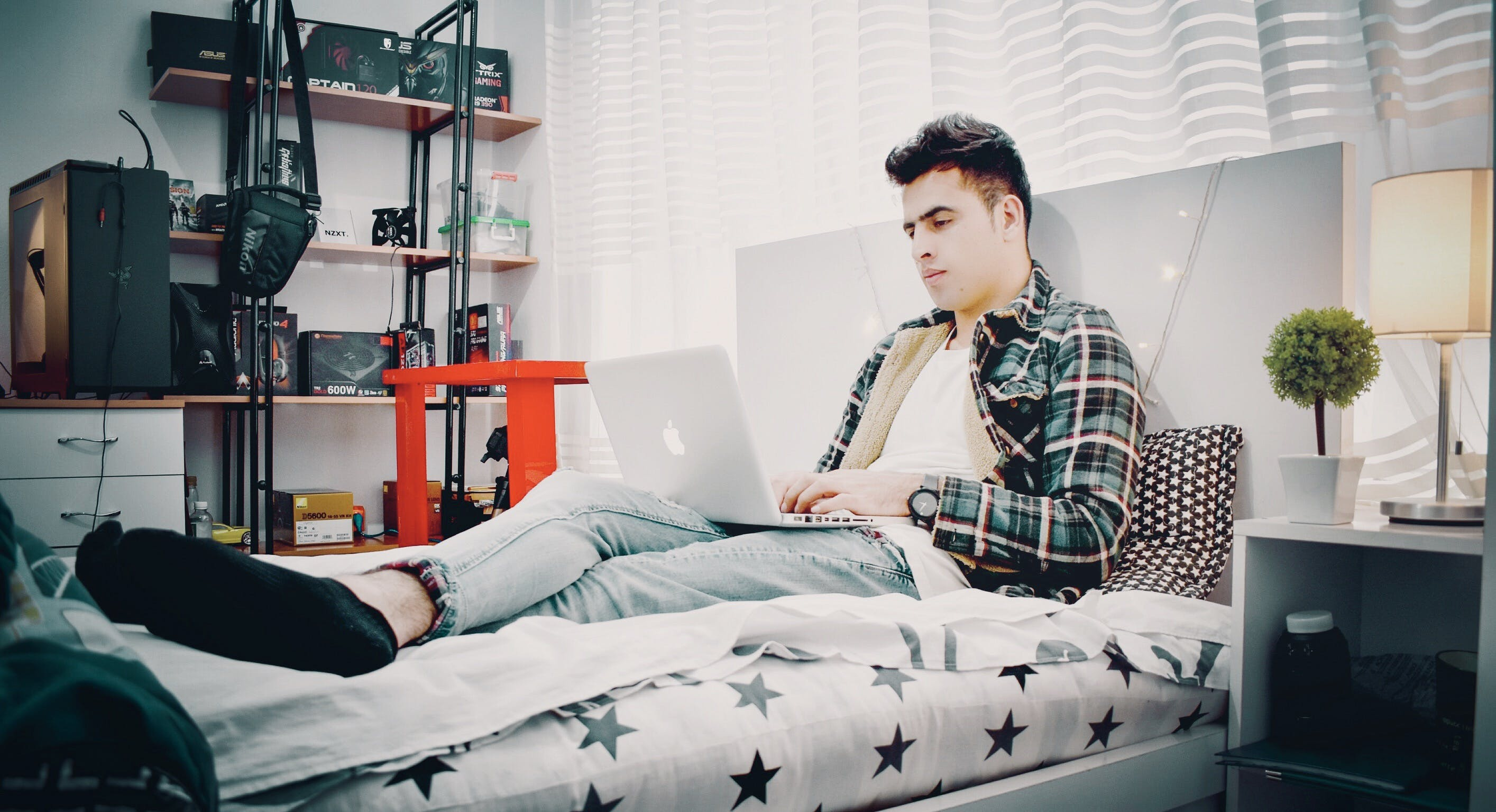 Man in Green, Blue, and Black Plaid Sports Shirt Sitting on Bed Using Silver Macbook