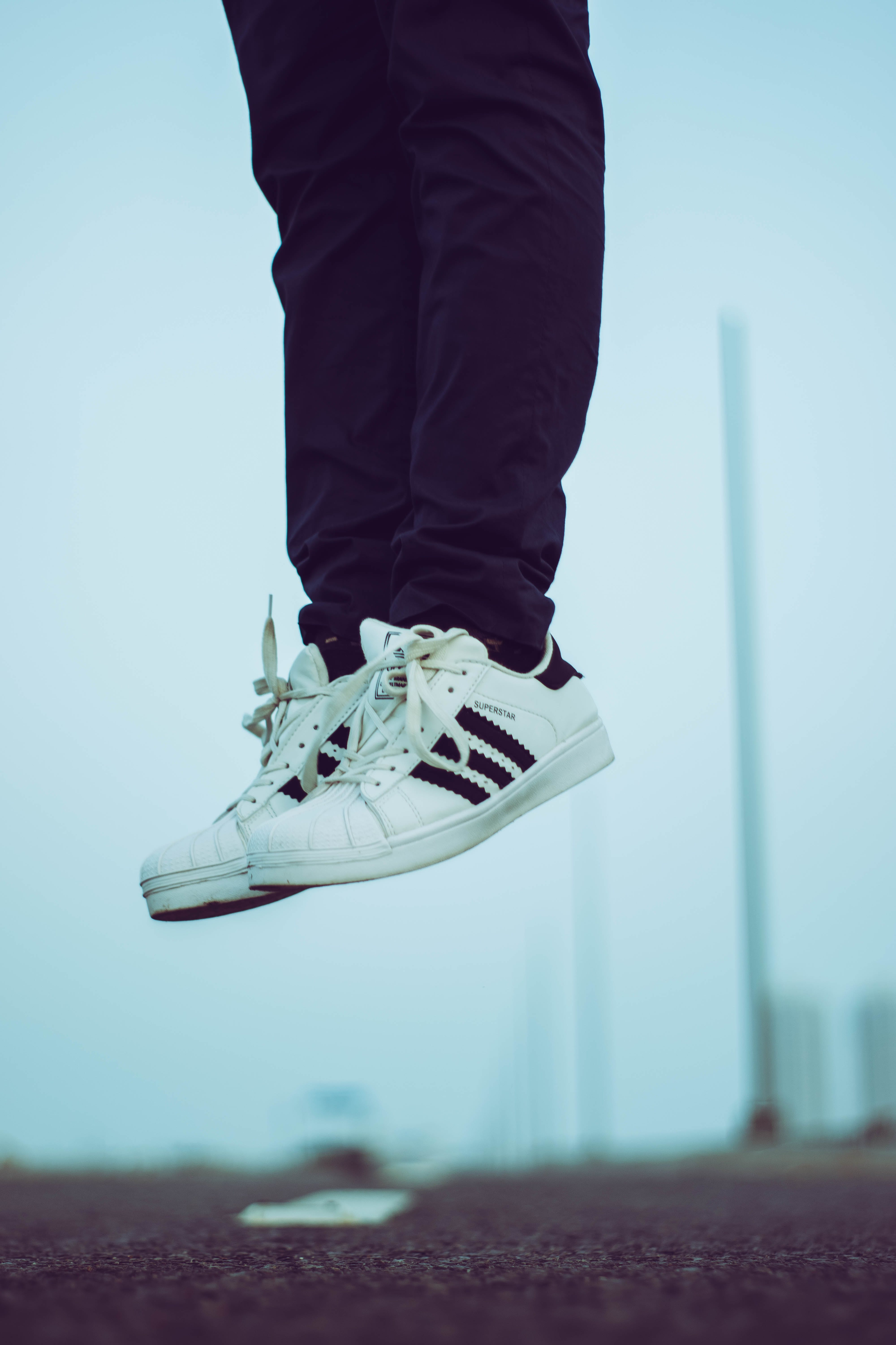 Person Wearing Pair of White Adidas Superstar Shoes