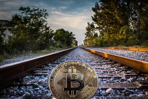 Gold-colored Bitcoin on Railroad