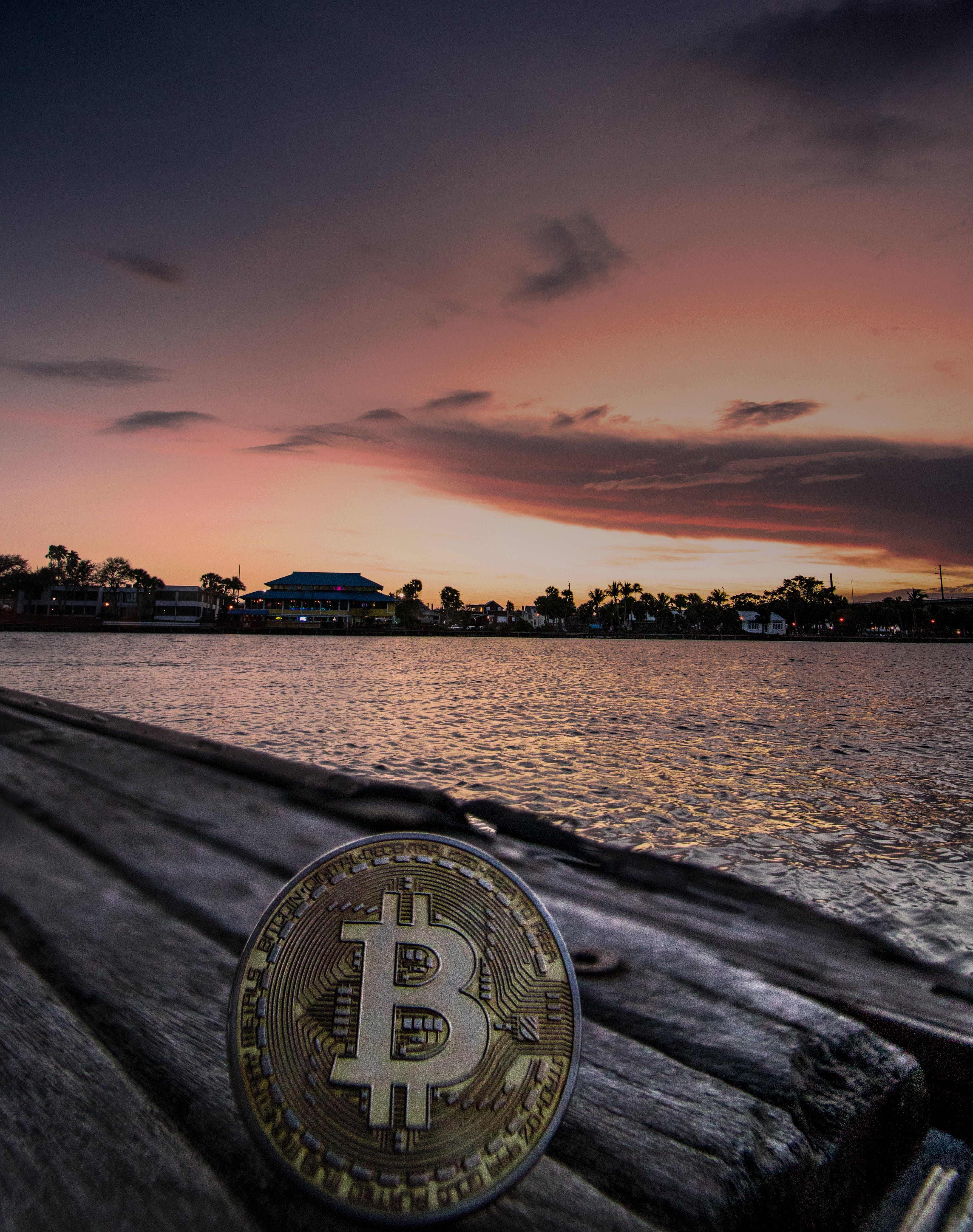 Body of Water during Dawn With Bitcoin Logo Text Overlay