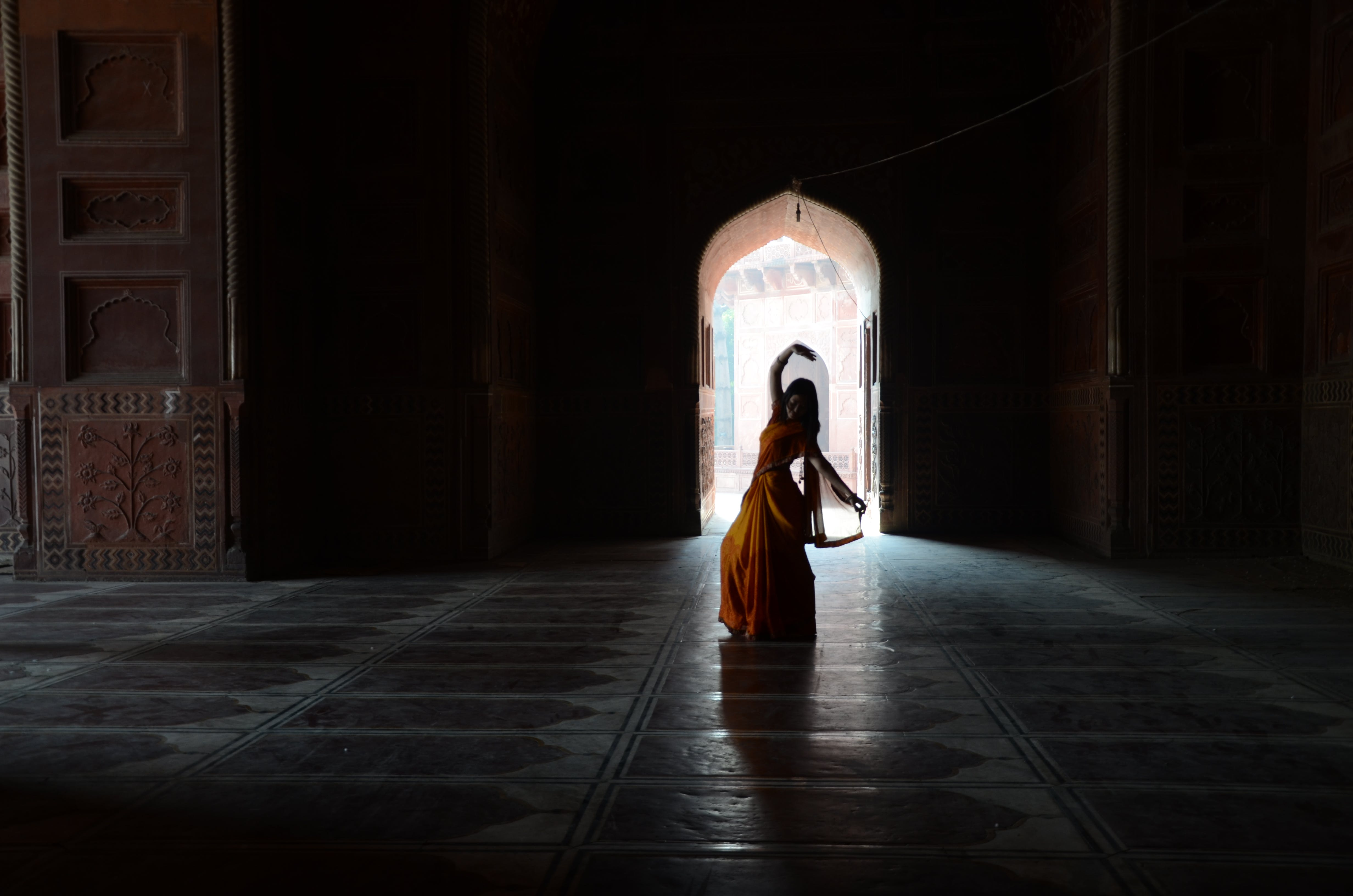 Woman in Orange and Yellow Traditional Dress Silhouette Inside Building