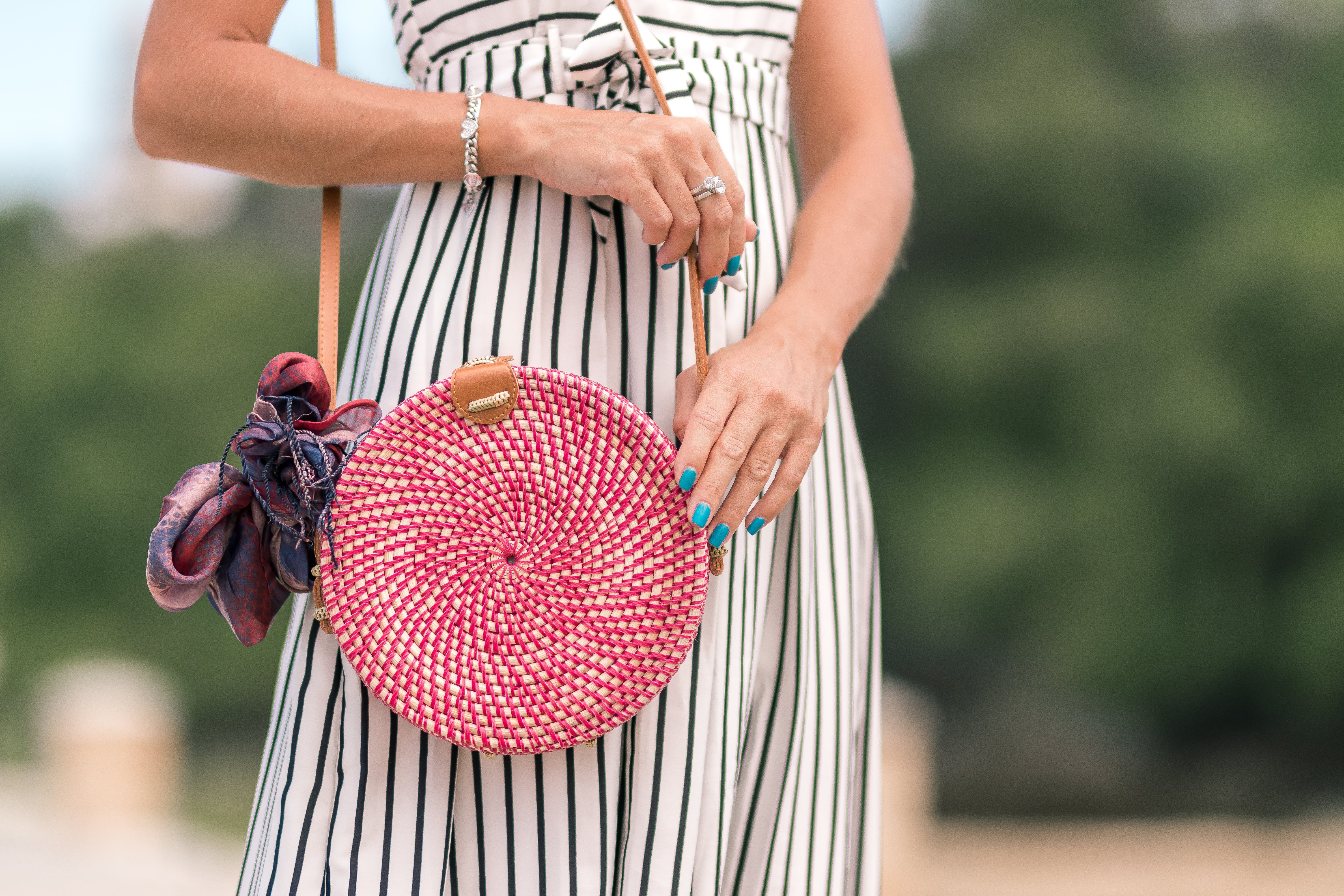 Woman Wearing White and Black Striped Dress Holding Her Red Sling Bag
