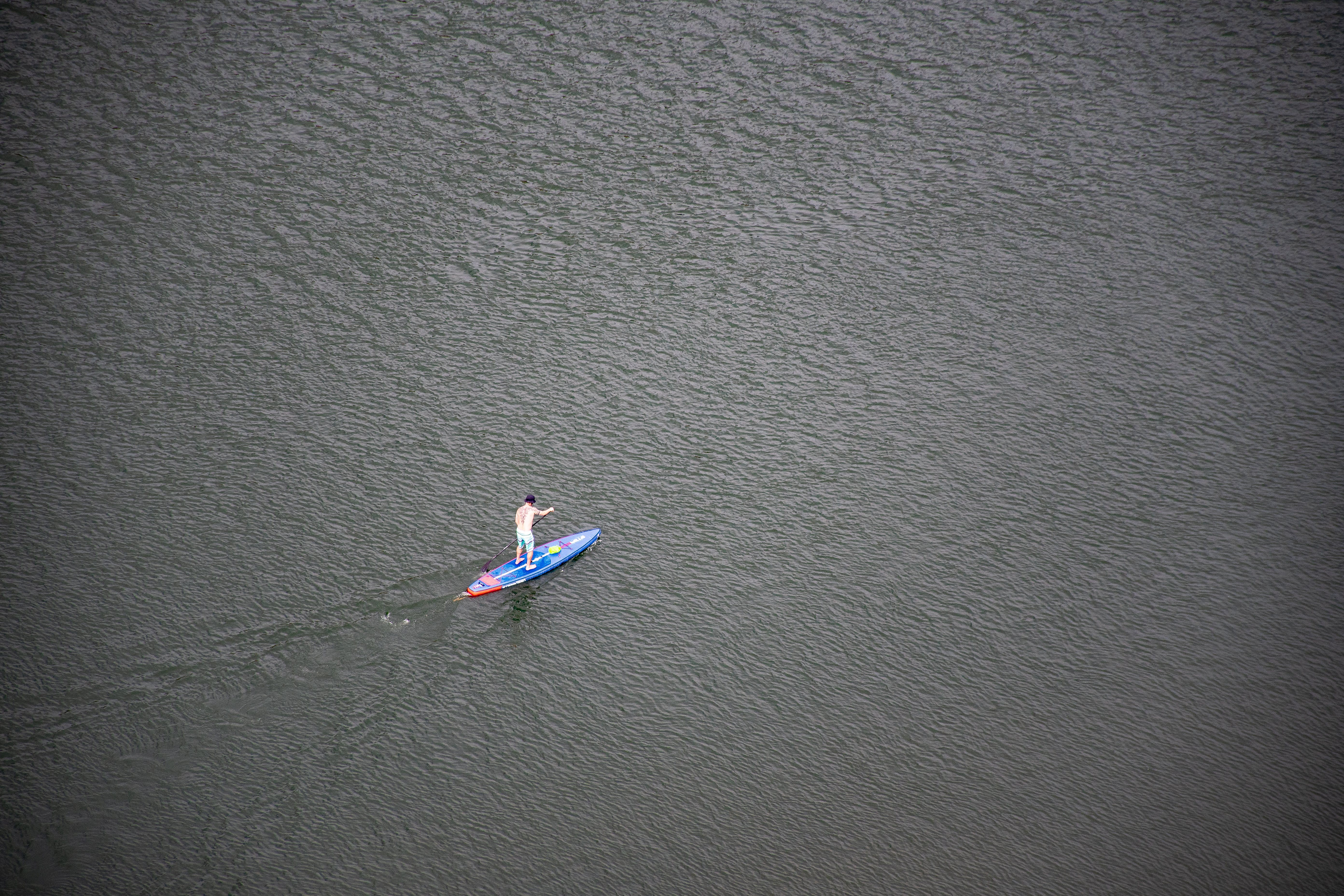 Person Riding Blue and Red Paddleboard on Water