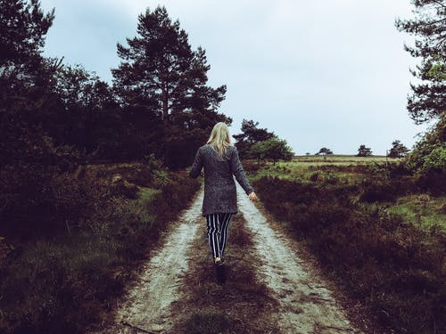 Woman in Grey Cardigan With Grey and Black Striped Pants Walking at the Pathway