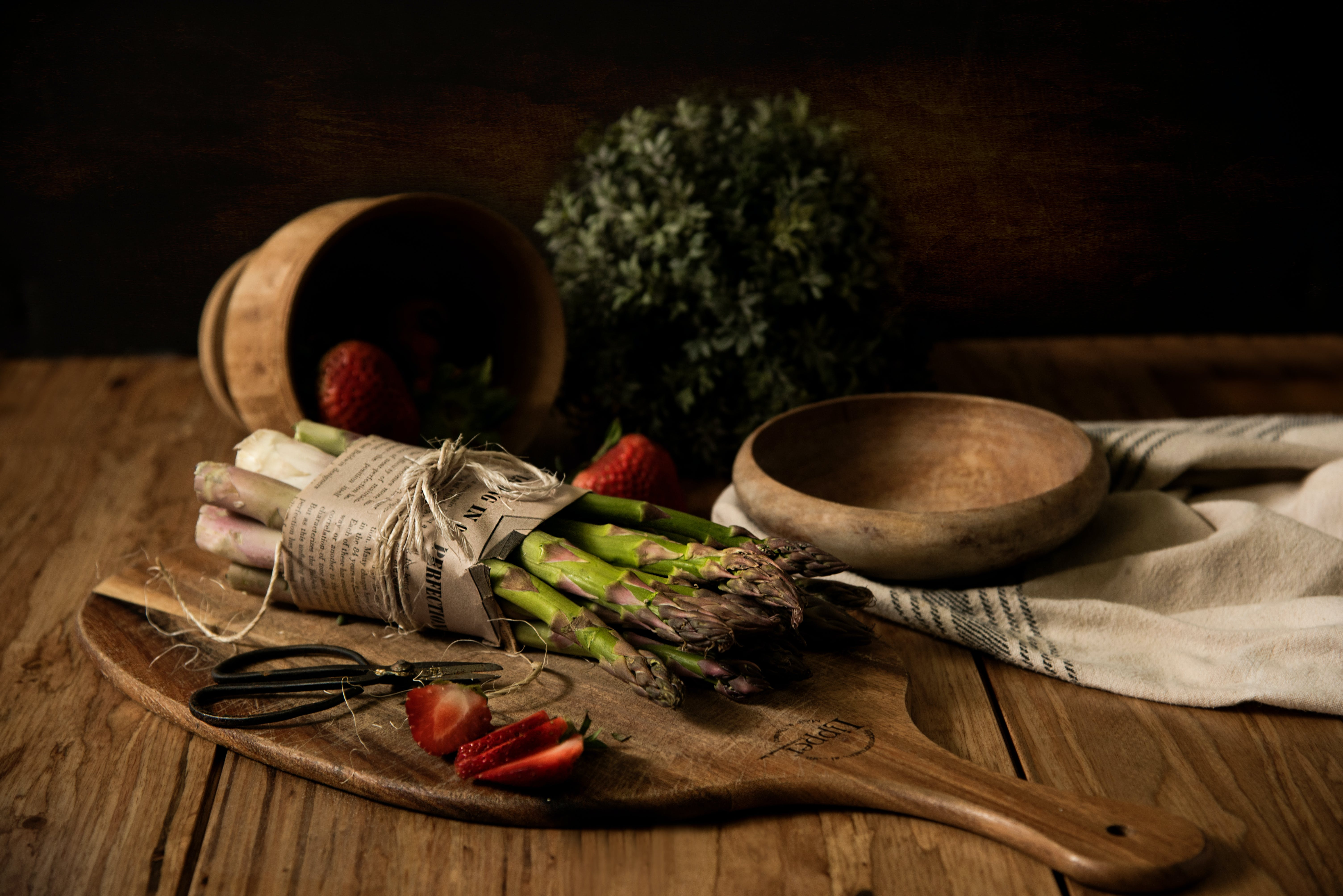 Asparagus on Wooden Board Beside Wooden Bowl