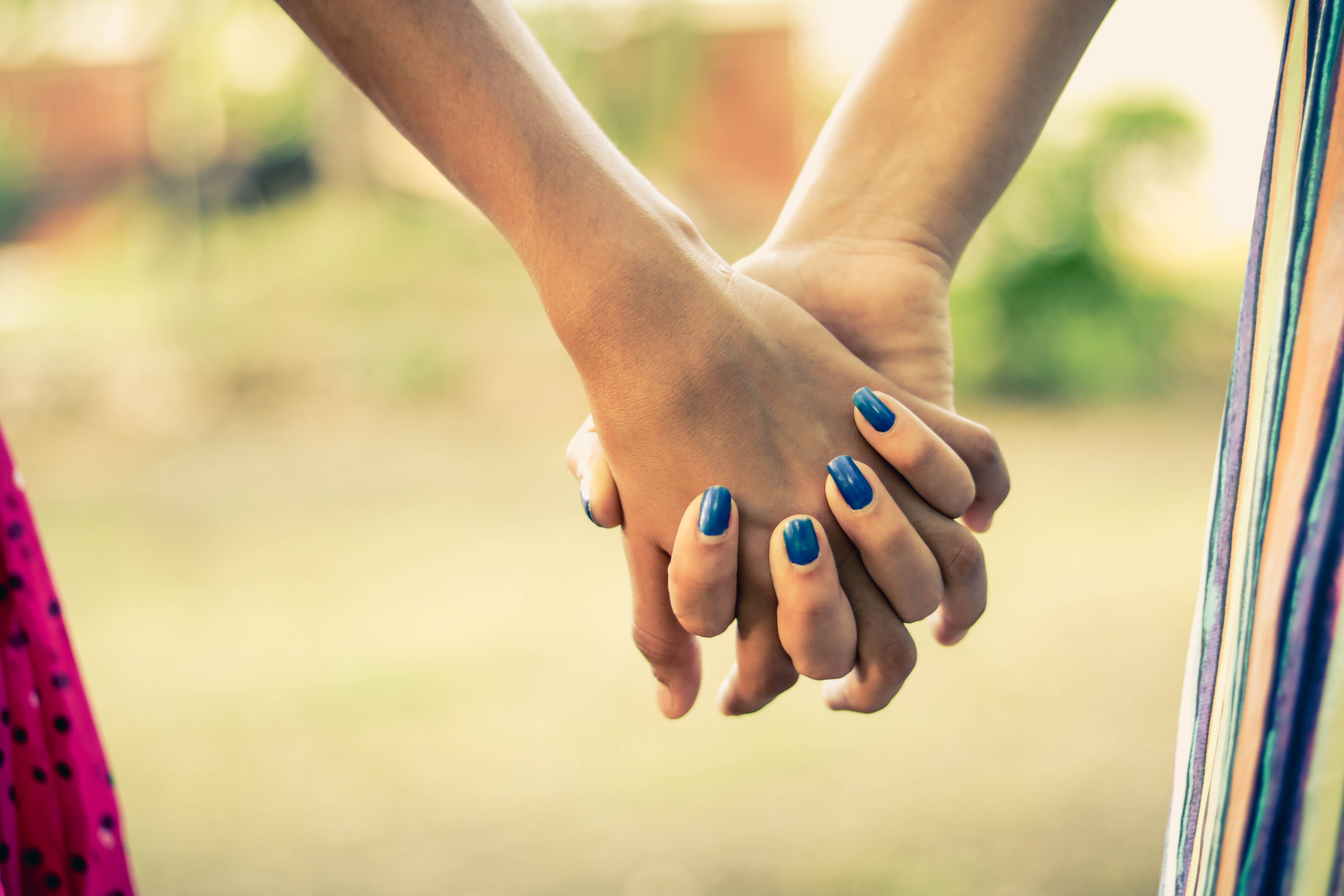 Shallow Focus Photography Of Two Person Holding Hands