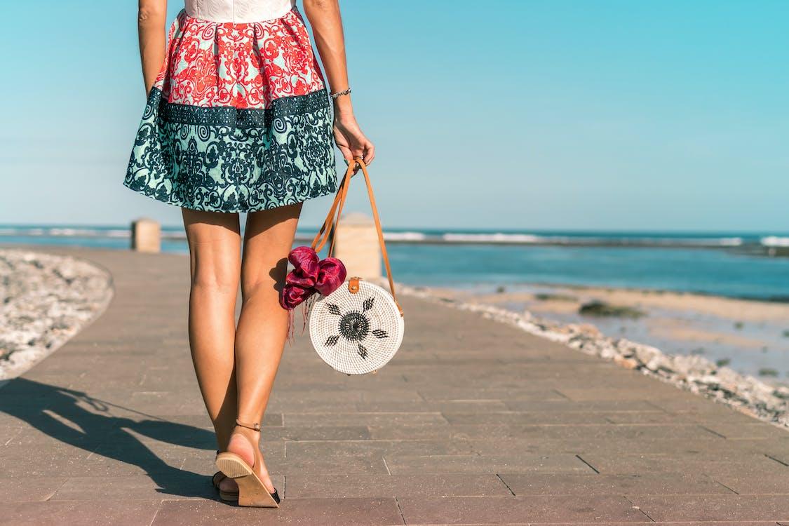 Woman Wearing Mini Skirt Holding Round Wicker Bag