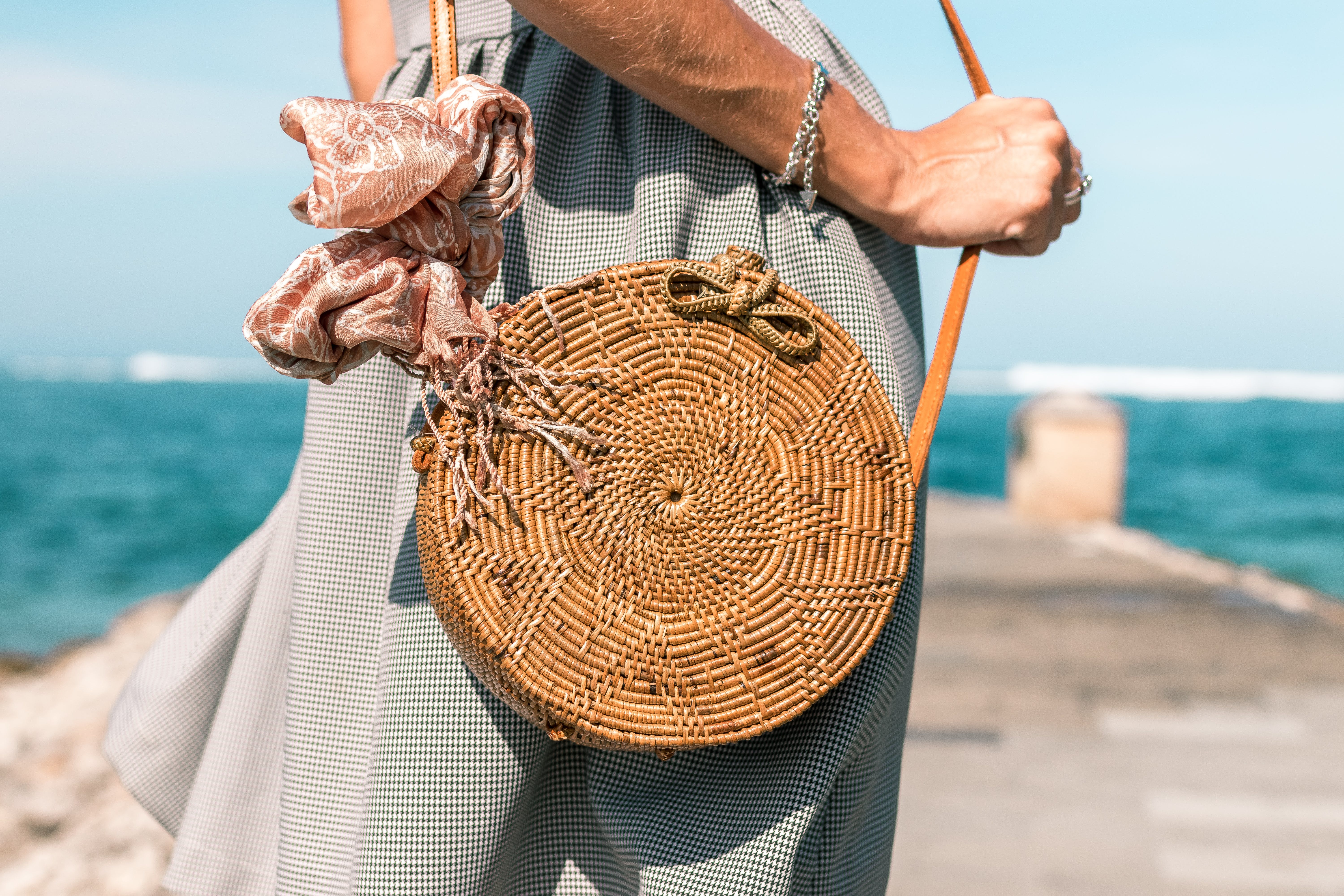 Woman Wearing Grey Skirt and Round Brown Rattan Crossbody Bag on Wooden Dock Near Body of Water