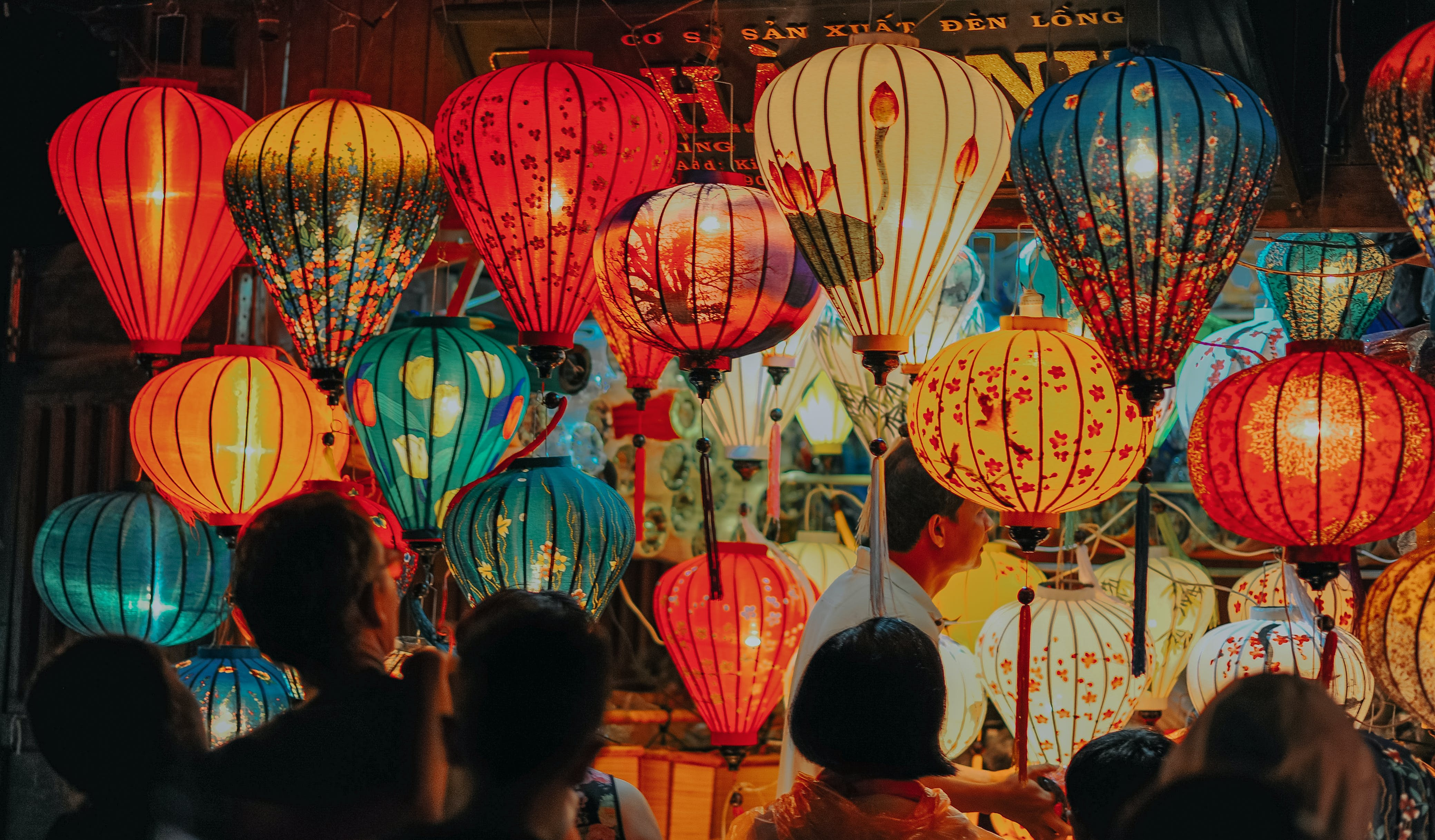 People Standing Near Assorted-color Lamps
