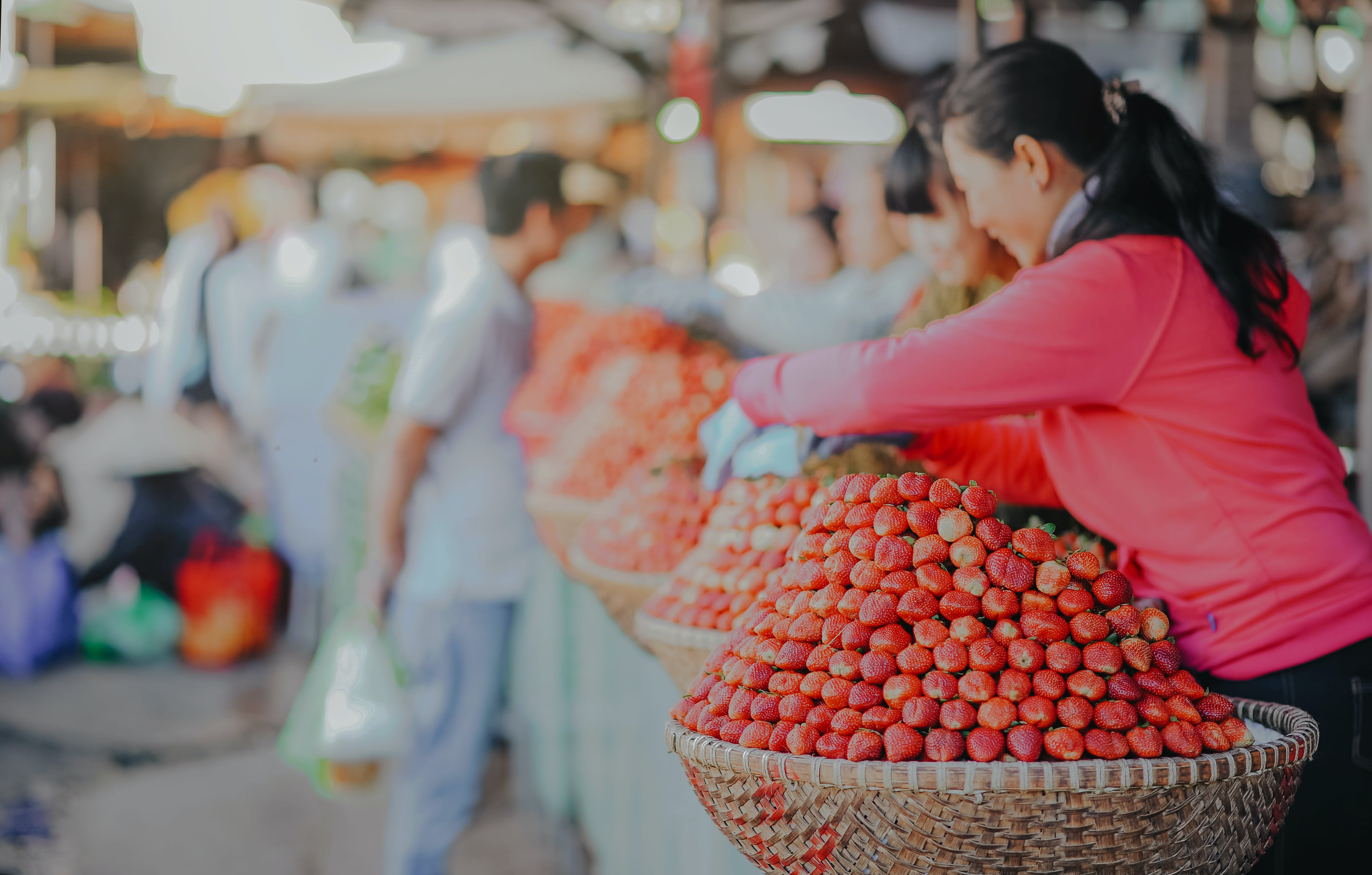 Selective Focus Photography Of Woman Wearing Red Hoodie Standing Behind Of Basket Full Of Fruits