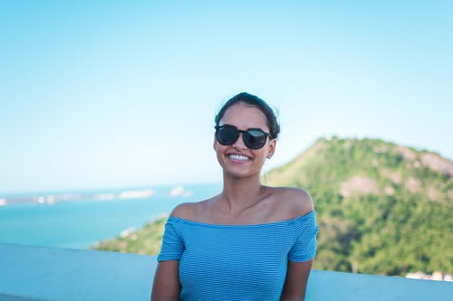 Smiling Woman Wearing Grey Striped Off-shoulder Top And Black Sunglasses