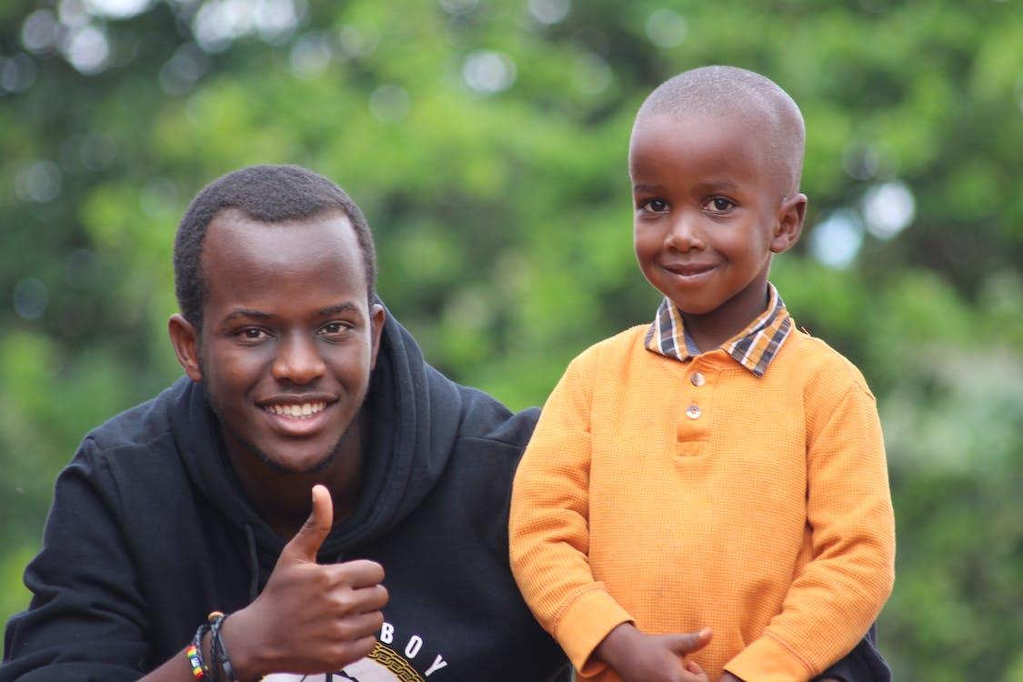 Man Wearing Black Hoodie Beside Boy Wearing Orange Long-sleeved Polo Shirt