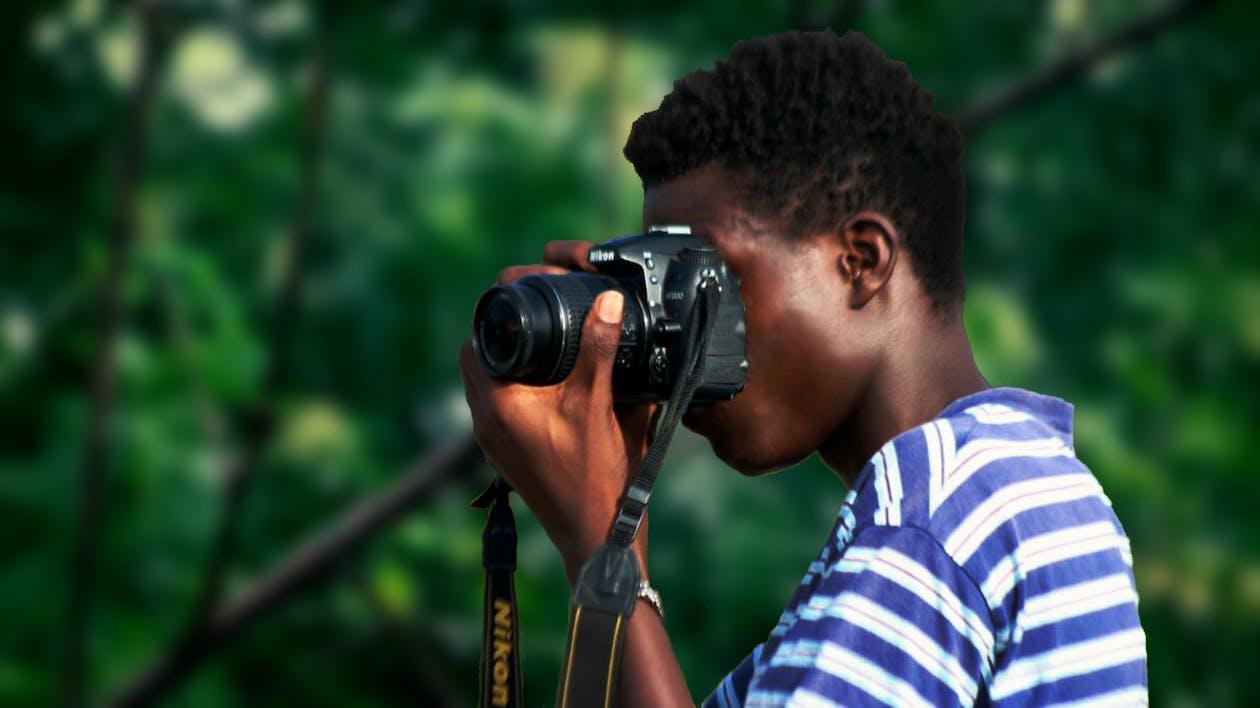 Man Wearing Blue And White Striped Shirt Using Nikon Camera