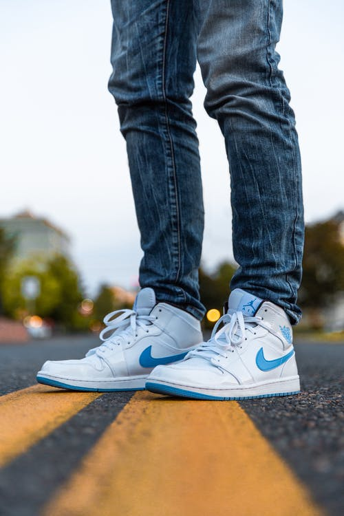 Person Wearing White And Blue Air Jordan 1's
