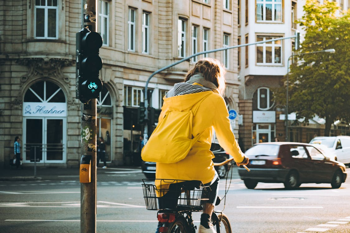 Woman Wearing Yellow Hooded Coat Riding Bicycle