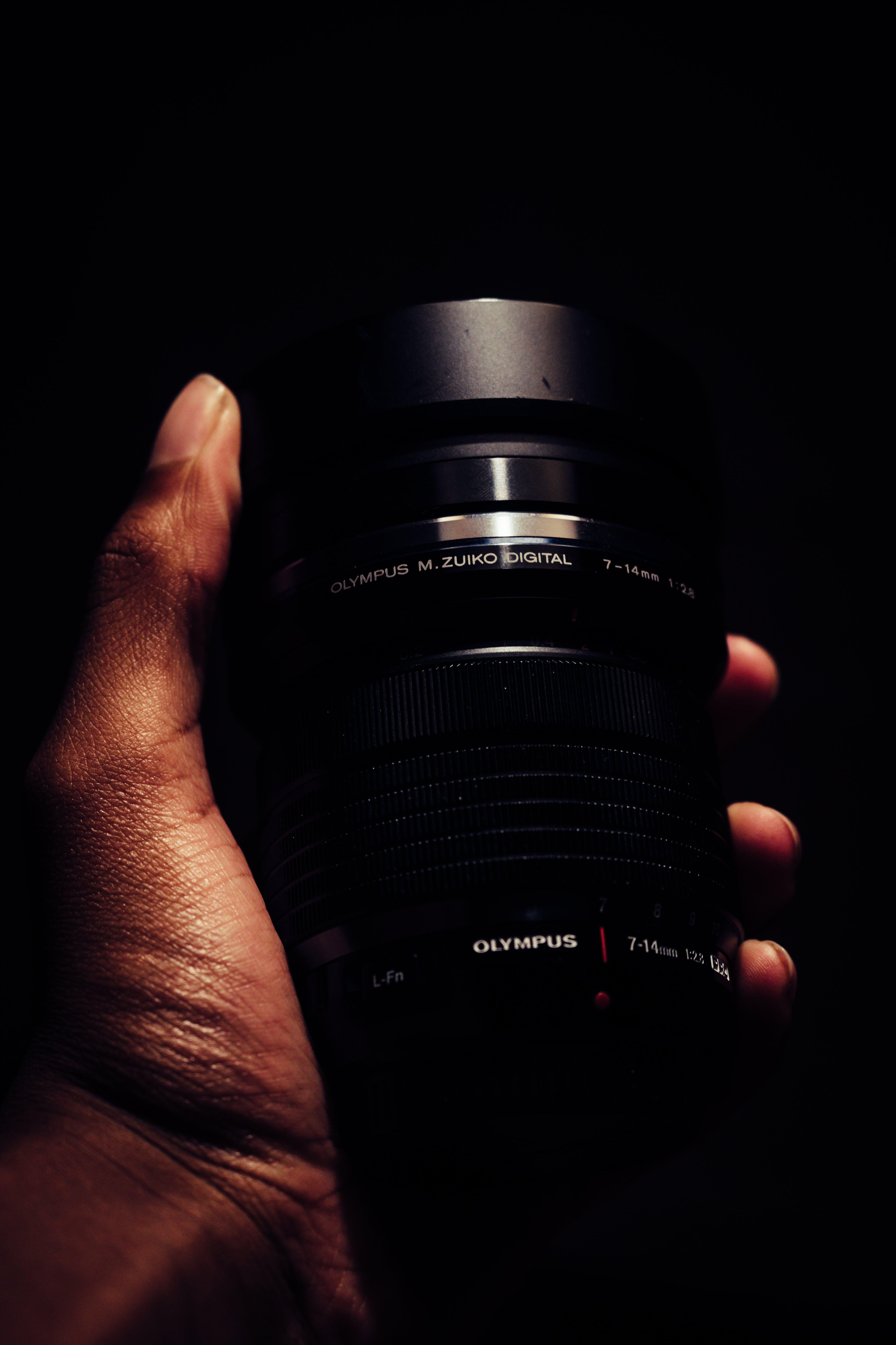 Person Holding Black Olympus Camera Lens