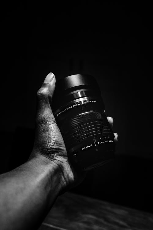 Person Holding Olympus Camera Lens