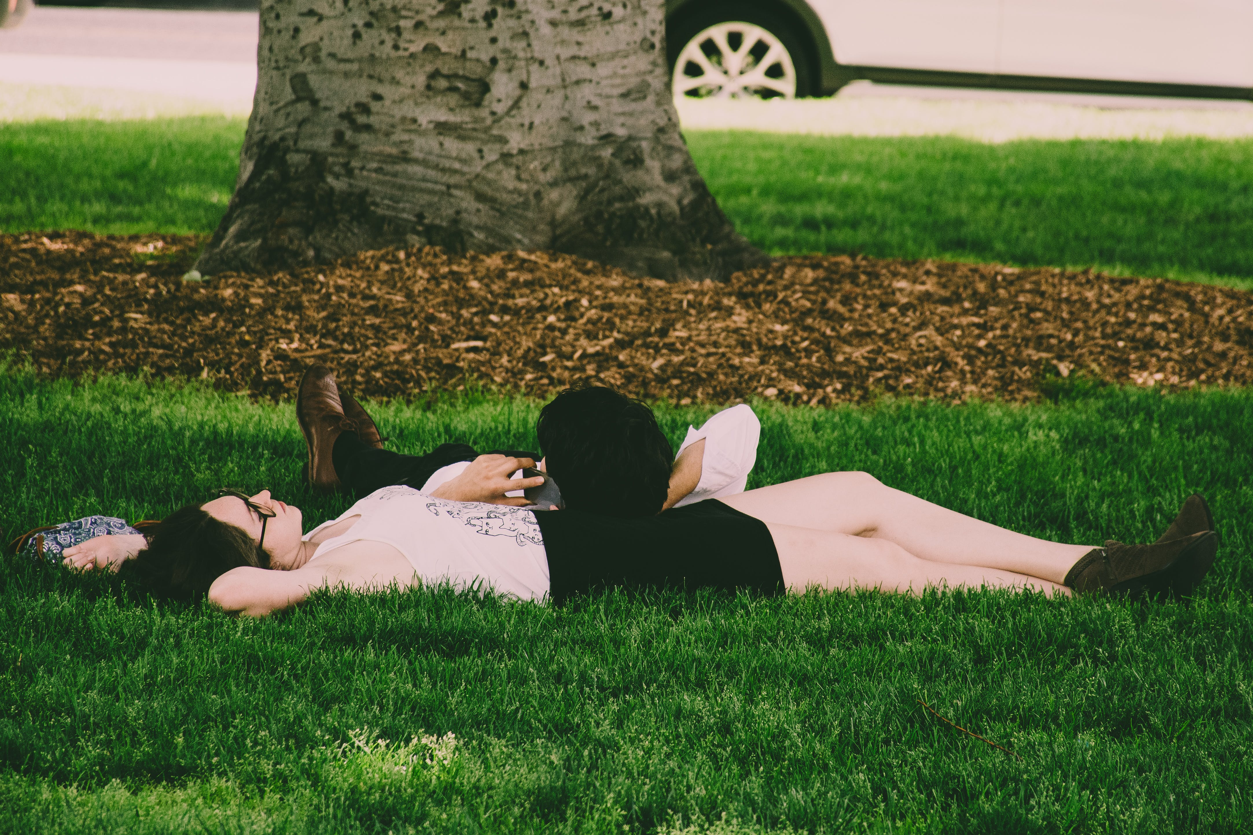 Woman Wearing White Tank Top Lying On Green Grass