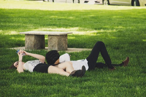 Man And Woman Laying On Green Grass Near Concrete Bench