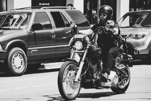Greyscale Photo Of Man Riding Motorcycle