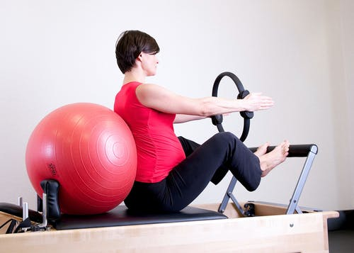 Woman in Red Top Leaning on Red Stability Ball