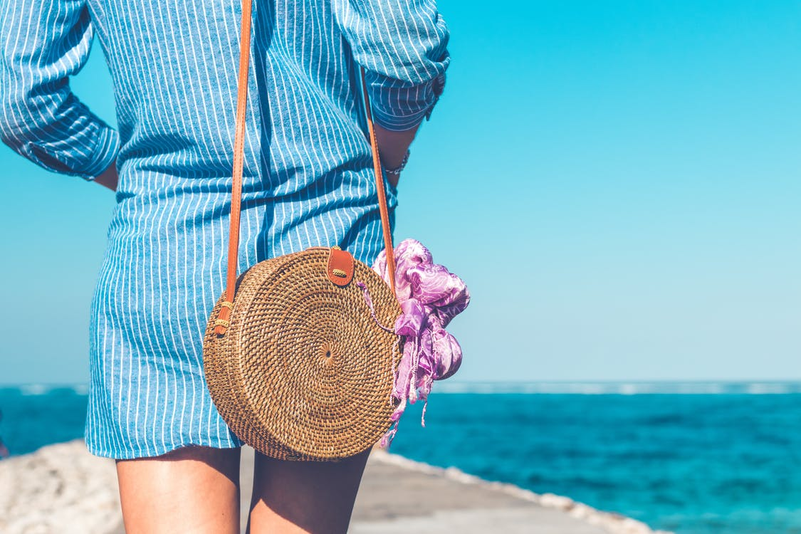 Woman Wearing Blue and White Striped Dress With Brown Rattan Crossbody Bag Near Ocean
