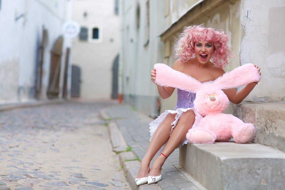 Woman Wearing Purple and Pink Dress Holding Rabbit Plush Toy