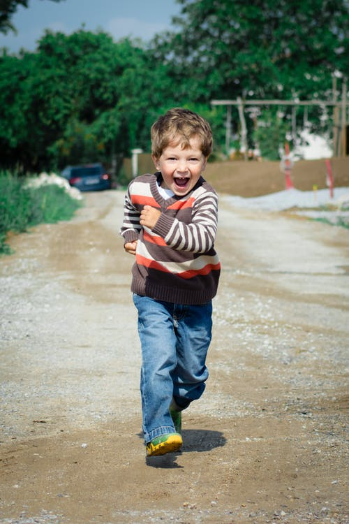 Boy Wearing Red, Brown, and White Stripe Sweater Running Photo