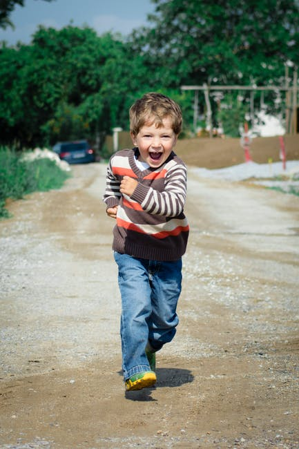 Boy wearing red brown and white stripe sweater running photo
