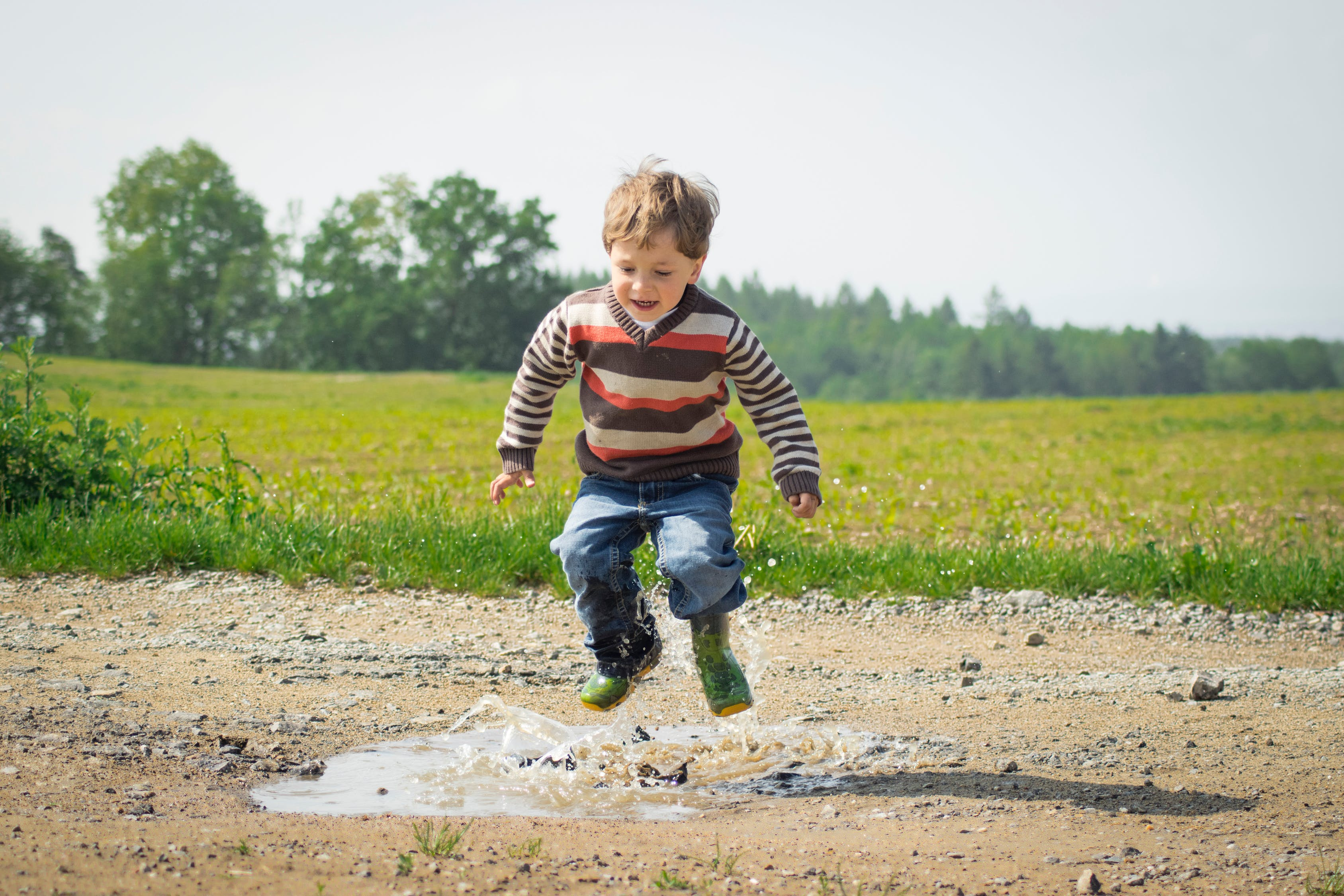 Child playing on a puddle