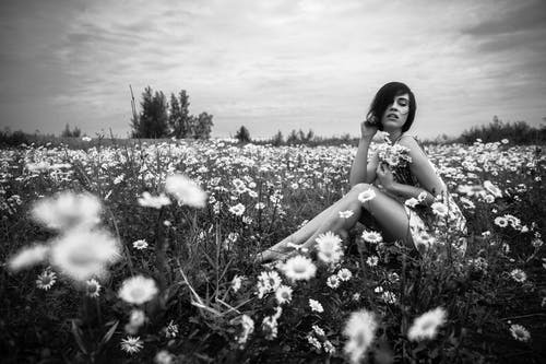 Grayscale Photo of Woman Sitting Beside Daisies