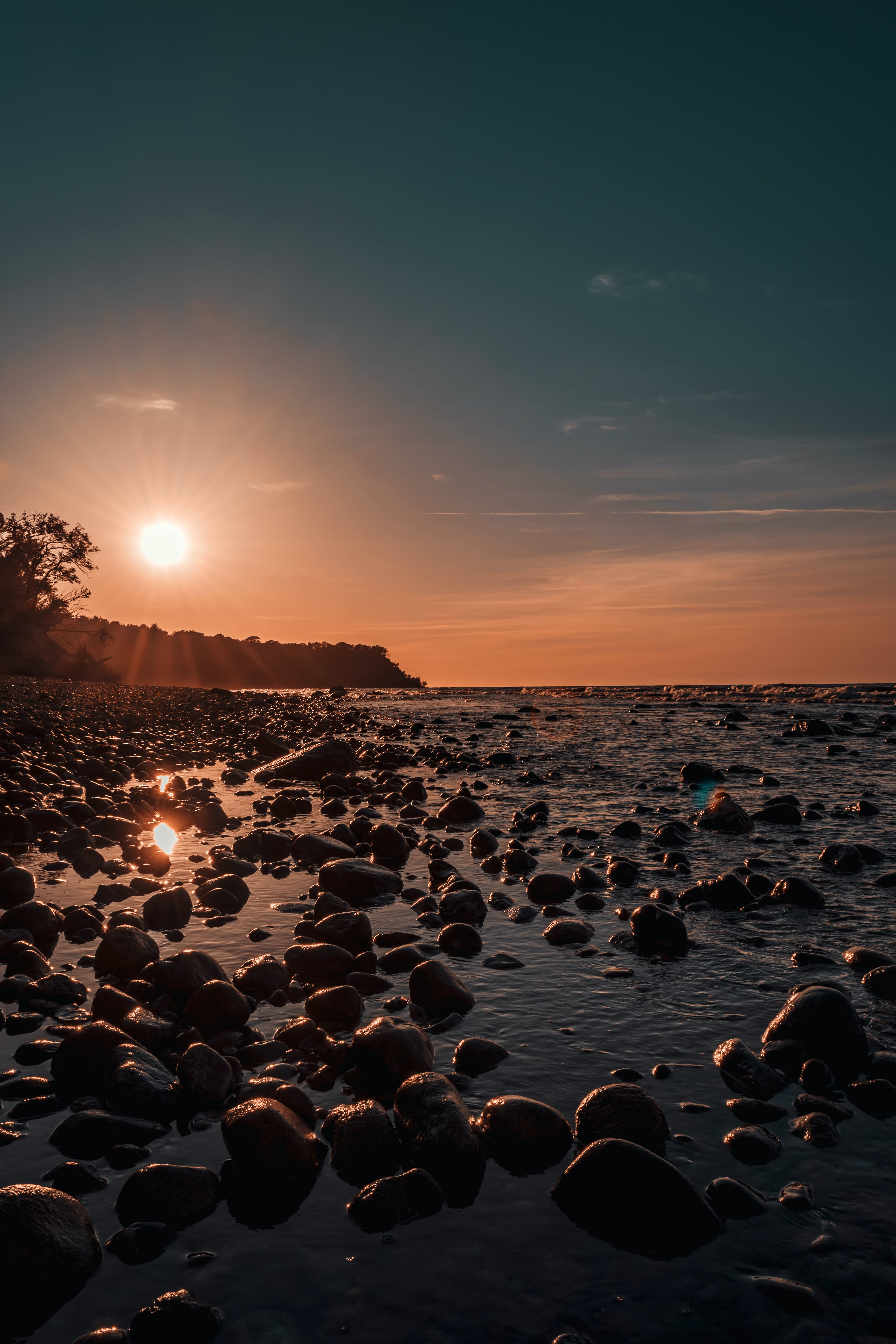 Photo Of Rock Rubles Beside Calm Body Of Water during Golden Hour
