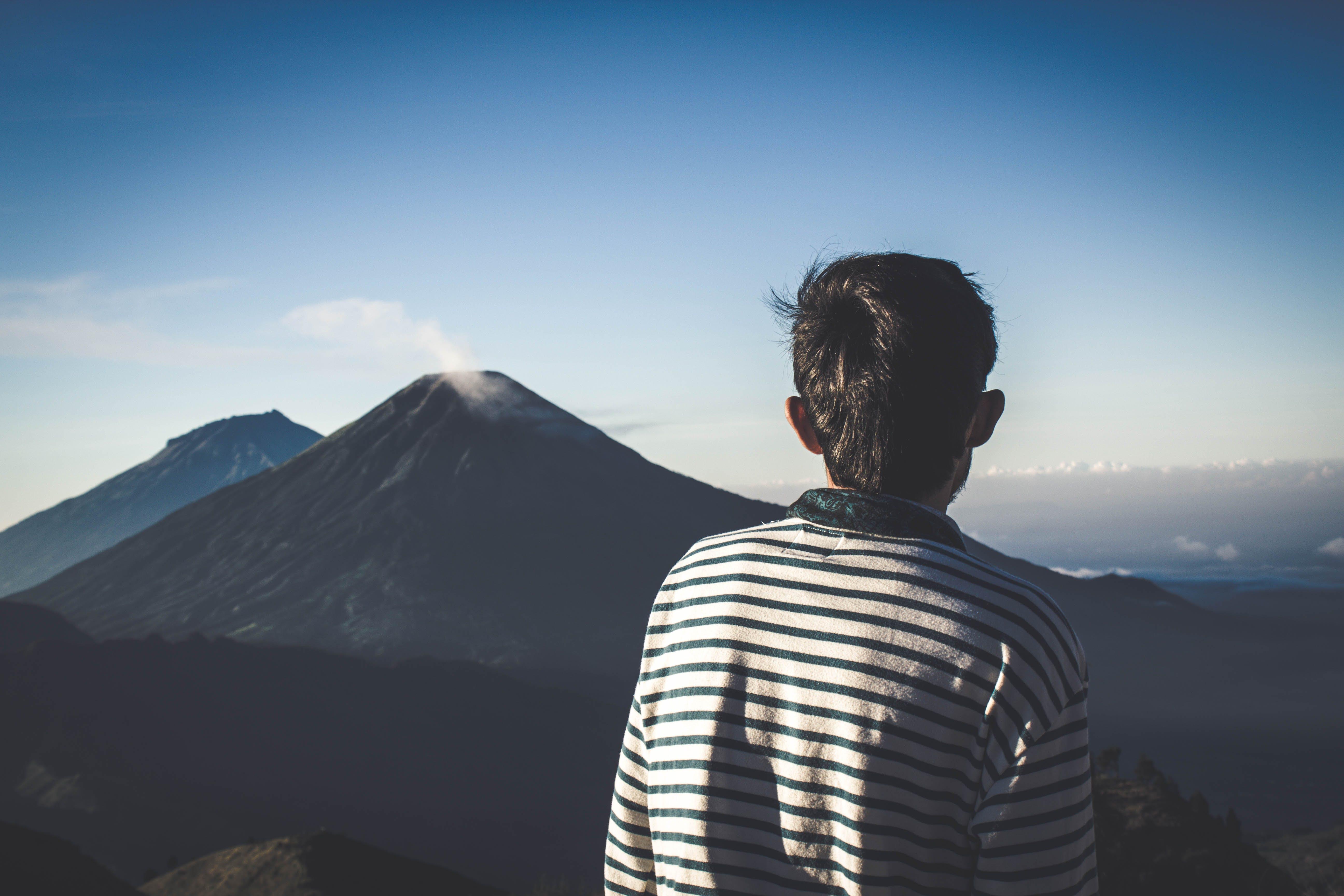 Man Wearing Striped Shirt Looking At Volcano