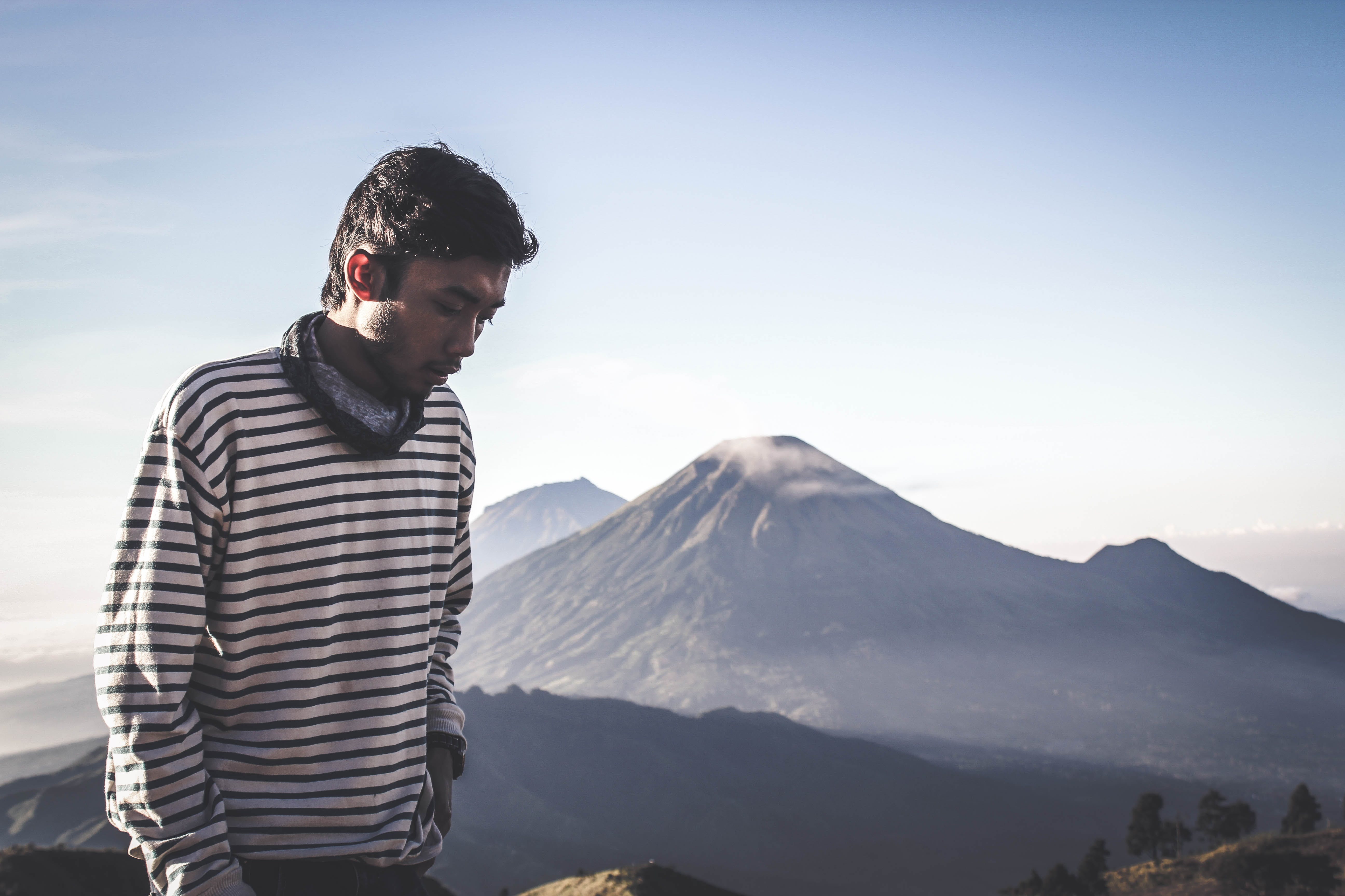 Person Wearing White and Black Striped Sweatshirt Standing in Front of Mountains