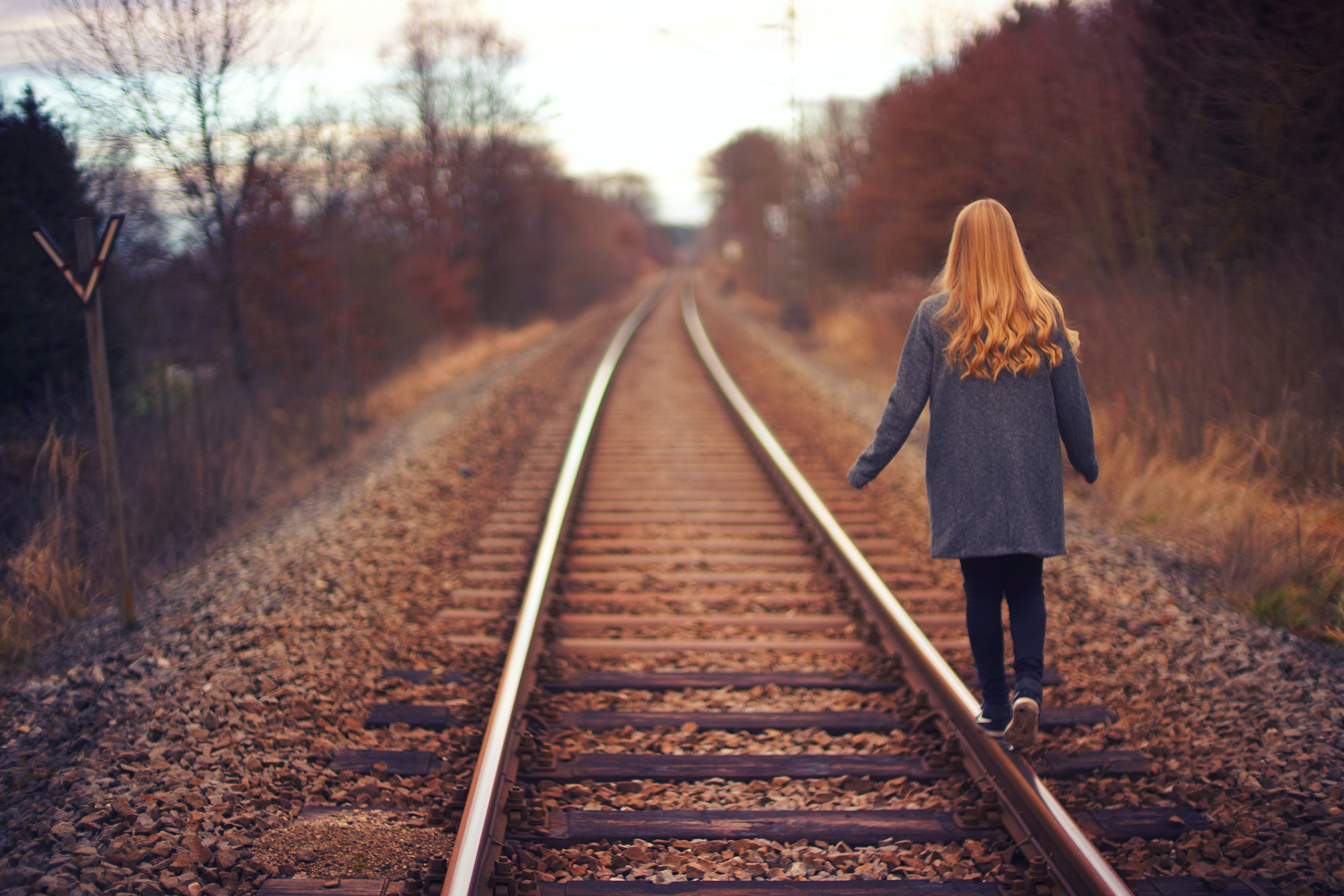 Woman in Blue Jacket and Blue Jeans Walking on Train Track Photography