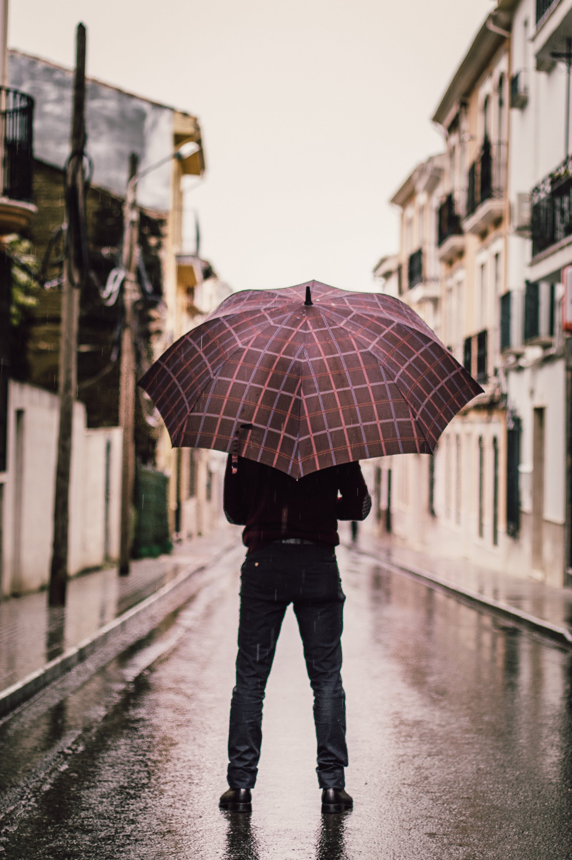 Person Wearing Black Pants Holding Umbrella Standing On Road